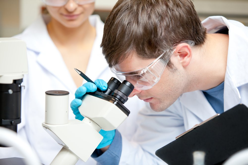 Caucasian male scientist holding pen and clipboard looking through a microscope in his laboratory
